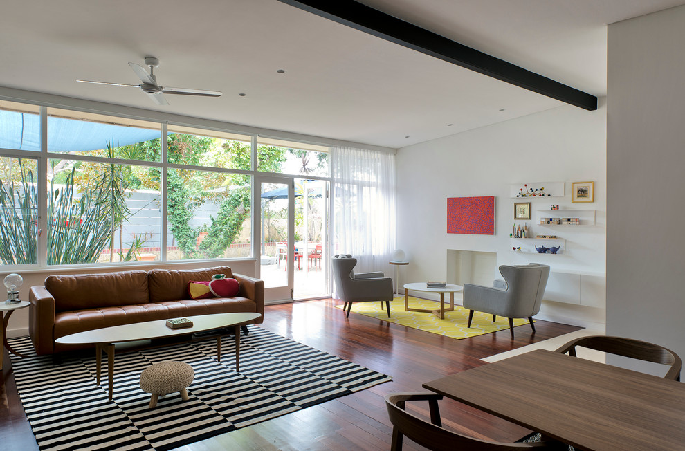 Example of a danish dark wood floor living room design in Perth with white walls