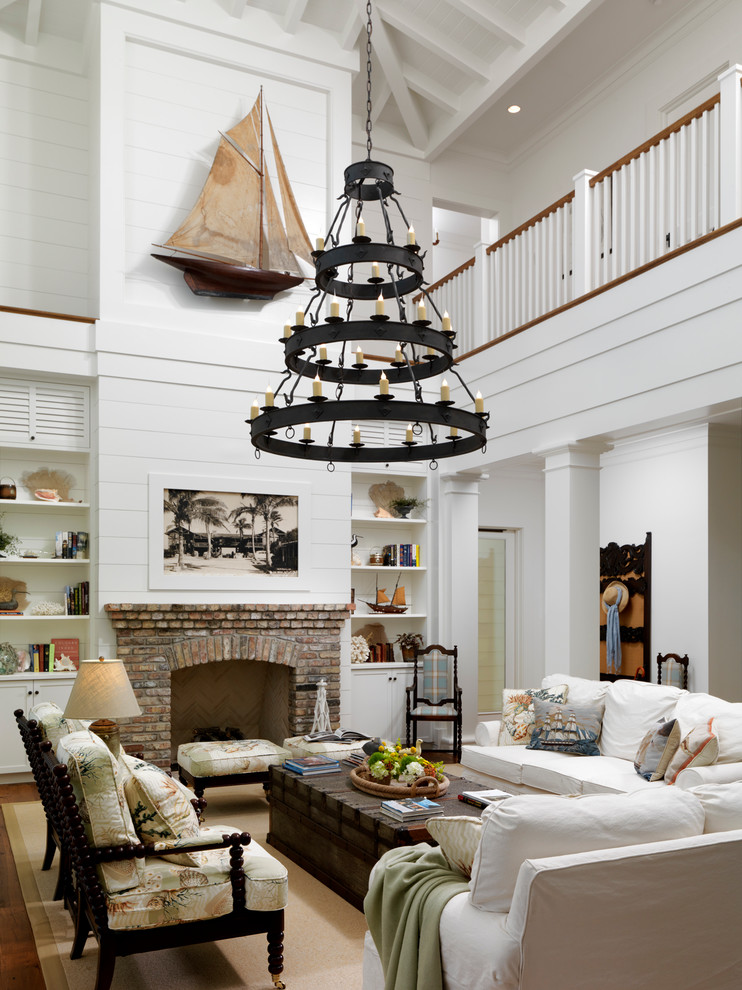 Example of a classic living room design in Orlando with white walls, a standard fireplace and a brick fireplace