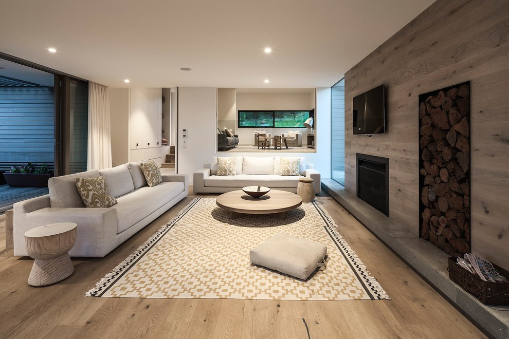 Large danish open concept light wood floor living room photo in Melbourne with white walls and a wall-mounted tv