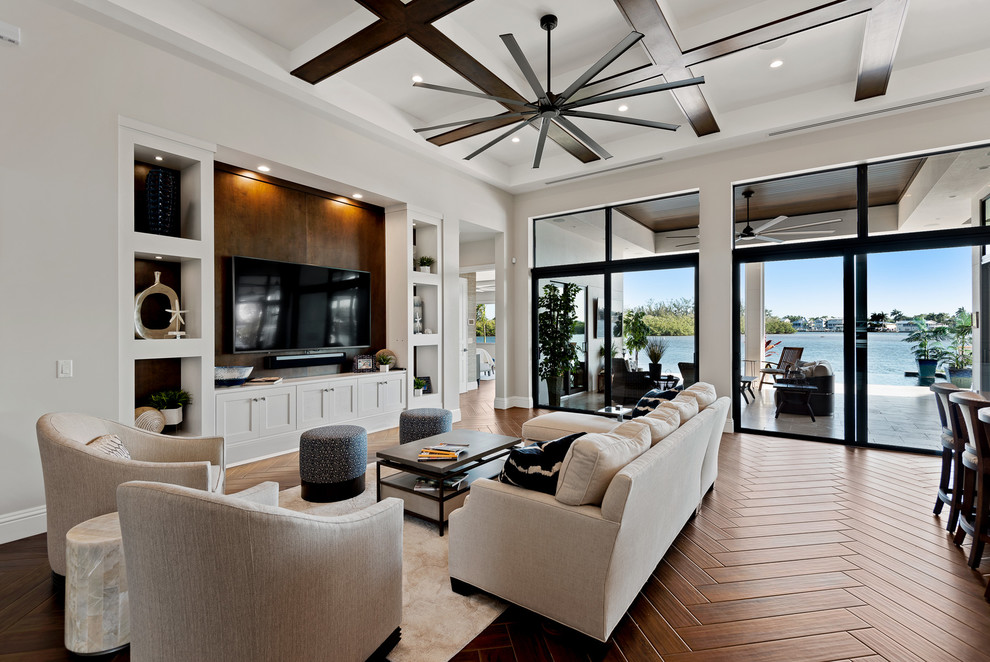 Example of a transitional open concept medium tone wood floor and brown floor living room design in Other with gray walls and a media wall