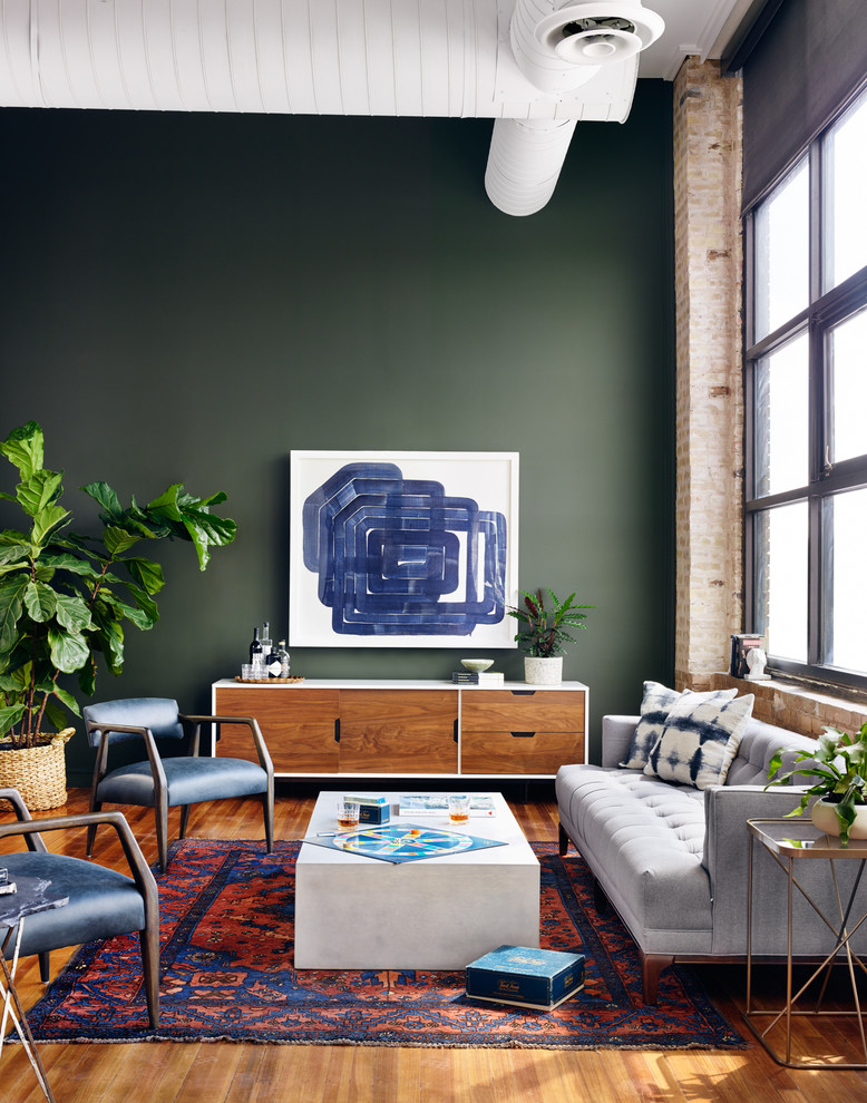 Inspiration for an industrial open concept medium tone wood floor living room remodel in Other with green walls, no fireplace and no tv