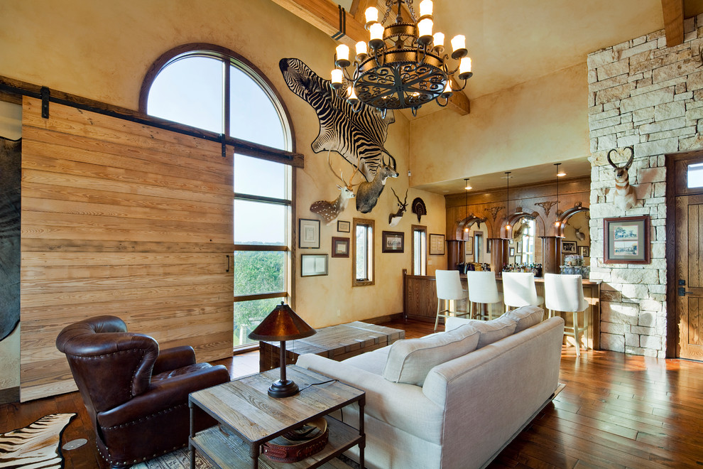 Large tuscan open concept dark wood floor and brown floor living room photo in Austin with a bar, beige walls, no fireplace and no tv