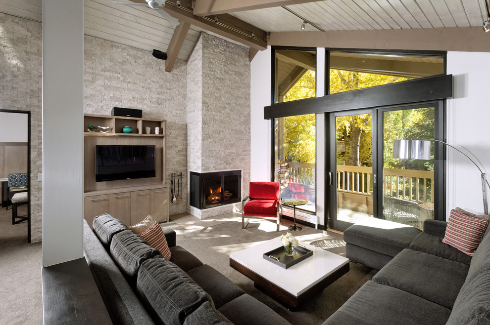 Inspiration for a large contemporary formal and open concept carpeted and gray floor living room remodel in Denver with white walls, a corner fireplace, a stone fireplace and a wall-mounted tv