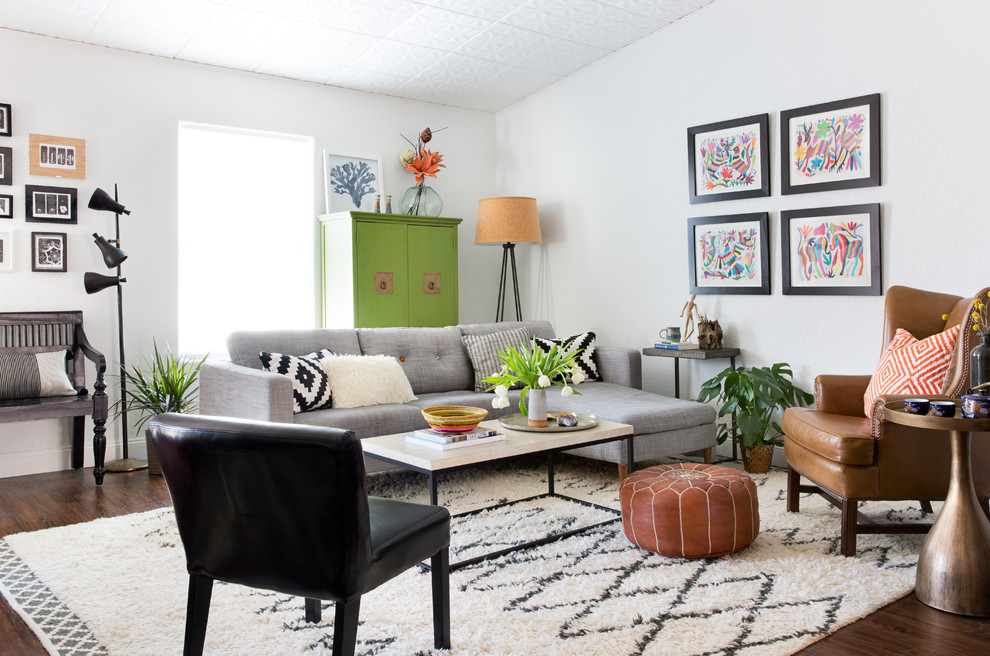 Example of an eclectic open concept dark wood floor and brown floor living room design in Austin with white walls