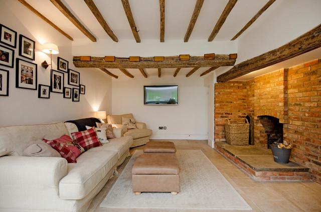 Ejemplo de salón de estilo de casa de campo con paredes blancas, chimenea tradicional, marco de chimenea de ladrillo y televisor colgado en la pared