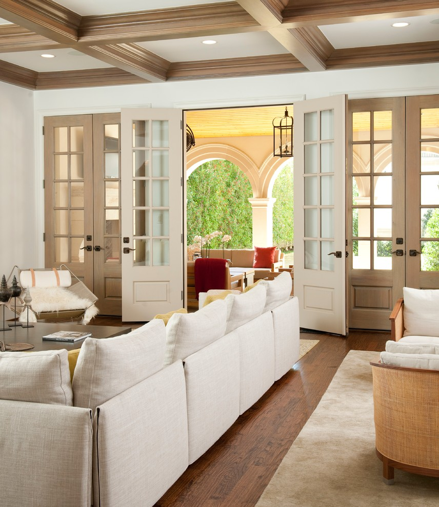 Tuscan medium tone wood floor living room photo in Dallas with white walls