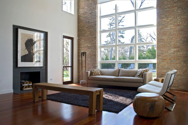 Example of a mid-sized trendy loft-style medium tone wood floor living room design in Chicago with white walls, a standard fireplace, a tile fireplace and no tv