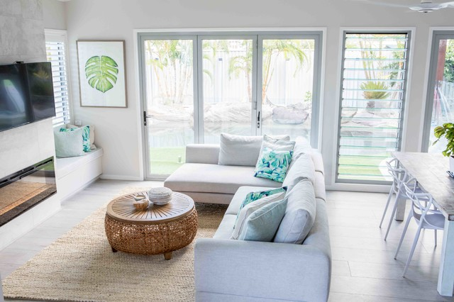 Mid-sized beach style open concept living room in Gold Coast - Tweed with white walls, painted wood floors, a standard fireplace, a stone fireplace surround and grey floor.