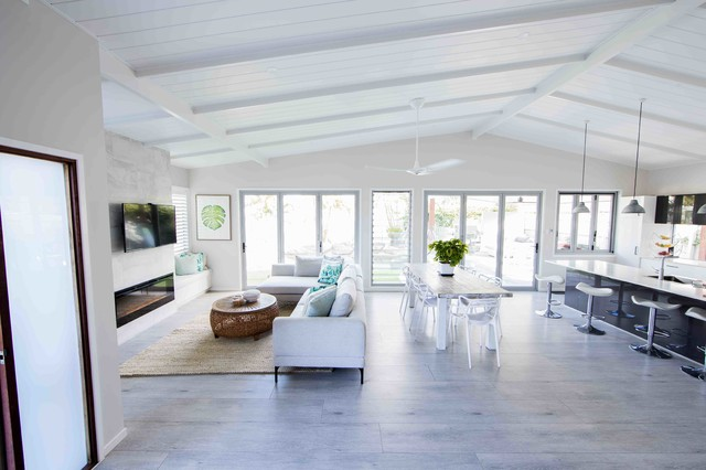 Photo of a mid-sized beach style open concept living room in Gold Coast - Tweed with white walls, painted wood floors, a standard fireplace, a stone fireplace surround and grey floor.