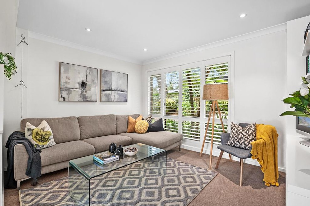 Living room - scandinavian carpeted and beige floor living room idea in Sydney with white walls