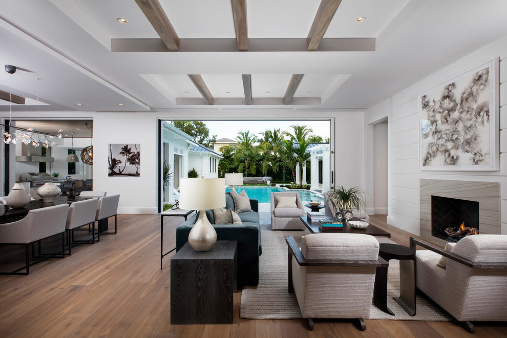 Living room - transitional open concept medium tone wood floor and brown floor living room idea in Miami with white walls, a stone fireplace and a standard fireplace