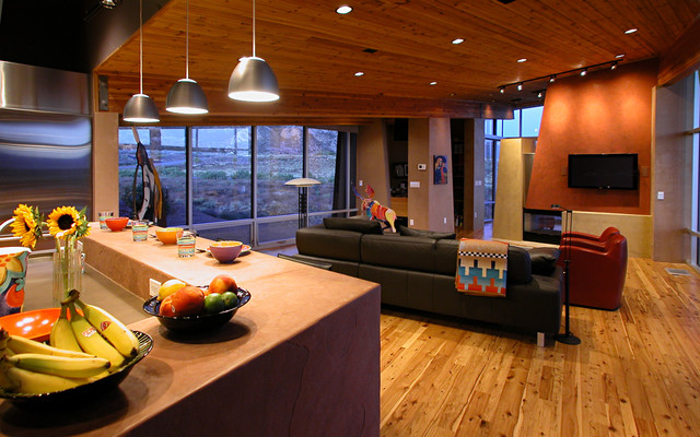 Living room - contemporary open concept medium tone wood floor living room idea in Denver with orange walls, a two-sided fireplace and a wall-mounted tv