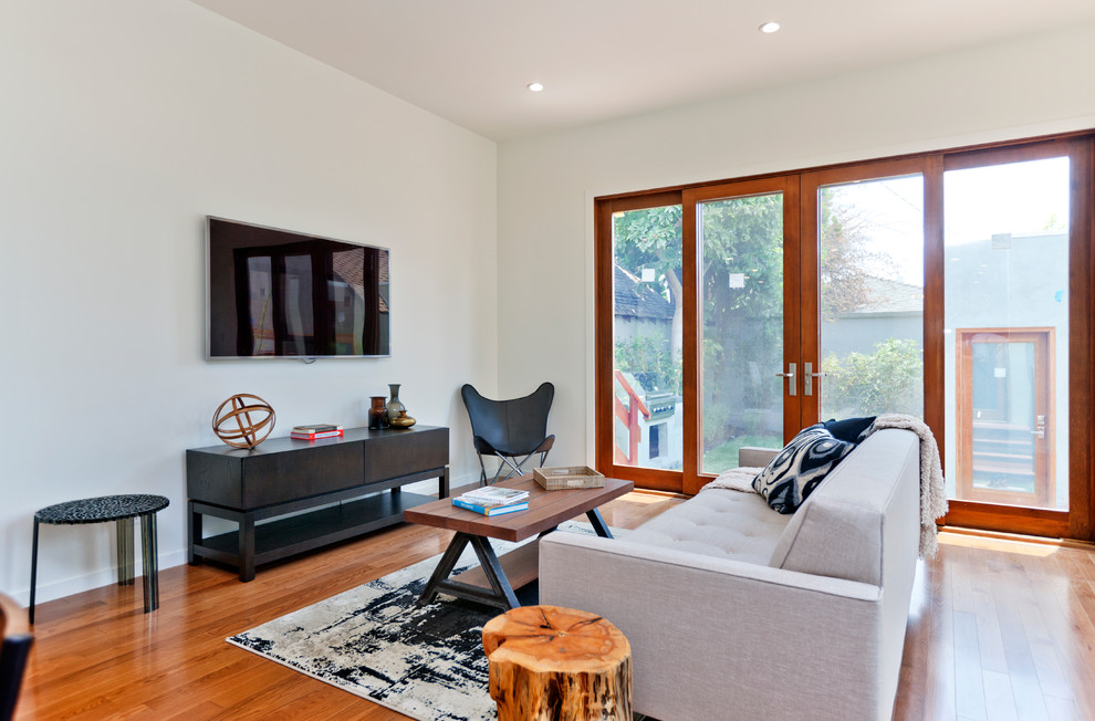 Living room - mid-sized transitional medium tone wood floor living room idea in Los Angeles with a wall-mounted tv