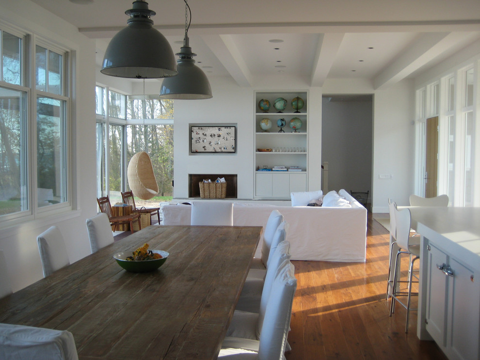 Inspiration for a coastal open concept medium tone wood floor and brown floor living room remodel in Milwaukee with white walls, a plaster fireplace and a concealed tv