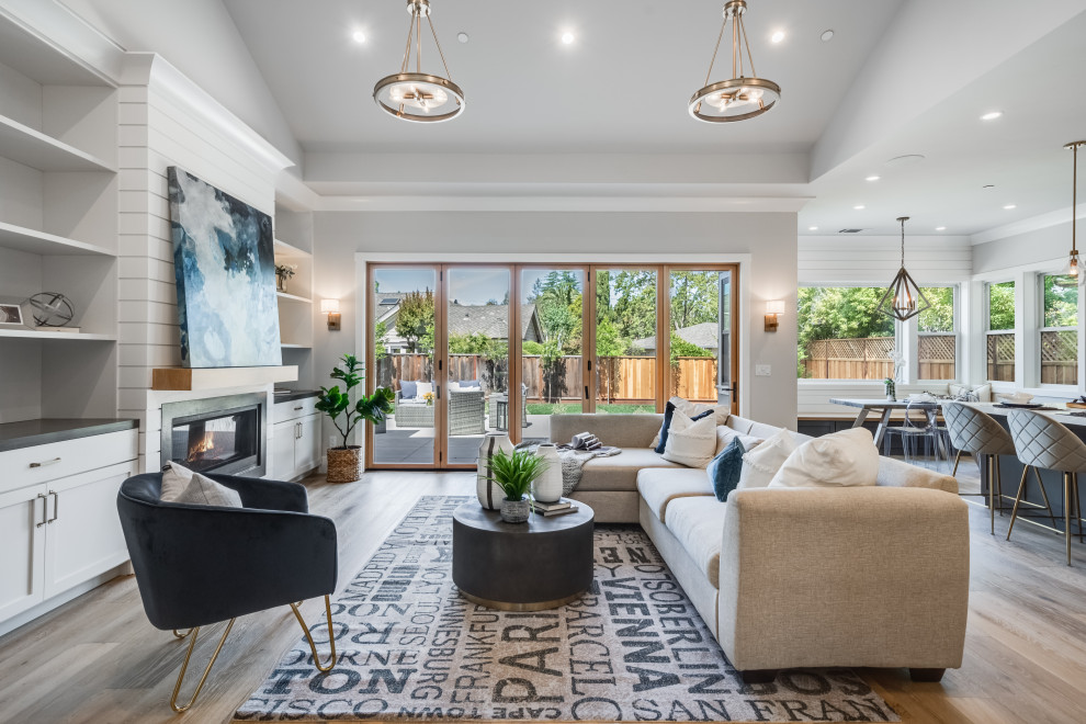 Large transitional open concept light wood floor, gray floor, vaulted ceiling and shiplap wall living room photo in San Francisco with gray walls, a ribbon fireplace, a stone fireplace and a wall-mounted tv