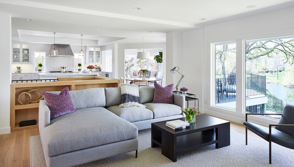 Mid-sized trendy open concept light wood floor and beige floor living room photo in Minneapolis with white walls, a wall-mounted tv, a two-sided fireplace and a plaster fireplace