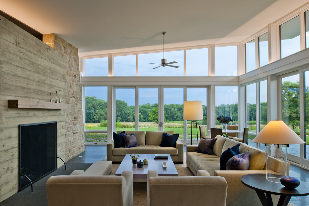 Example of a minimalist living room design in DC Metro with a standard fireplace and a wood fireplace surround