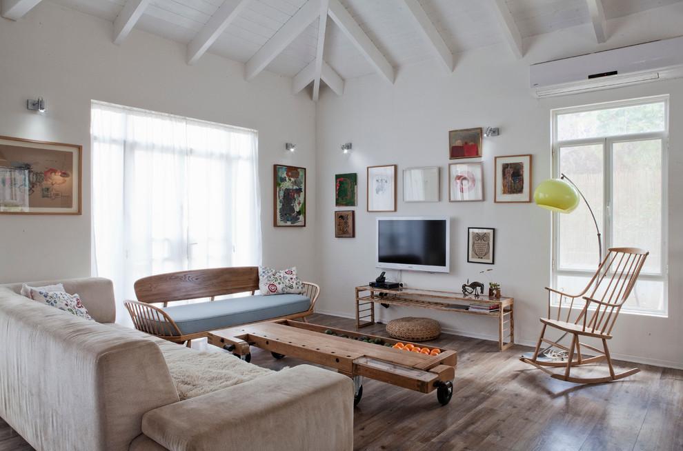 Example of a trendy medium tone wood floor living room design in Tel Aviv with white walls