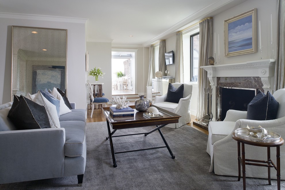 Example of a mid-sized transitional formal and enclosed medium tone wood floor living room design in New York with gray walls, a standard fireplace, a stone fireplace and no tv
