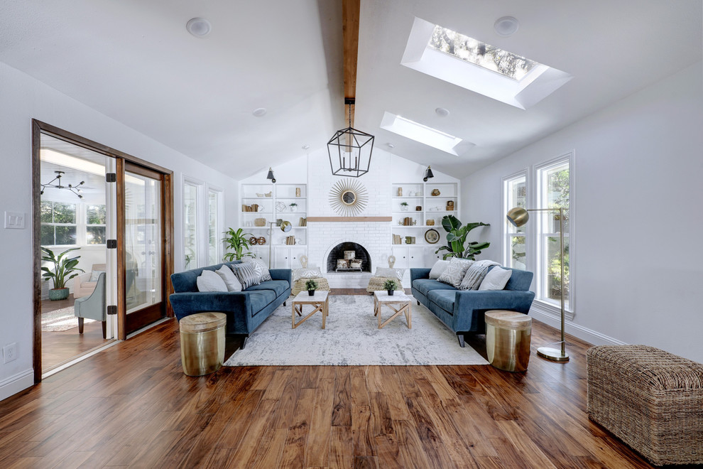 Inspiration for a cottage formal and enclosed medium tone wood floor and brown floor living room remodel in Austin with white walls, a standard fireplace and a brick fireplace