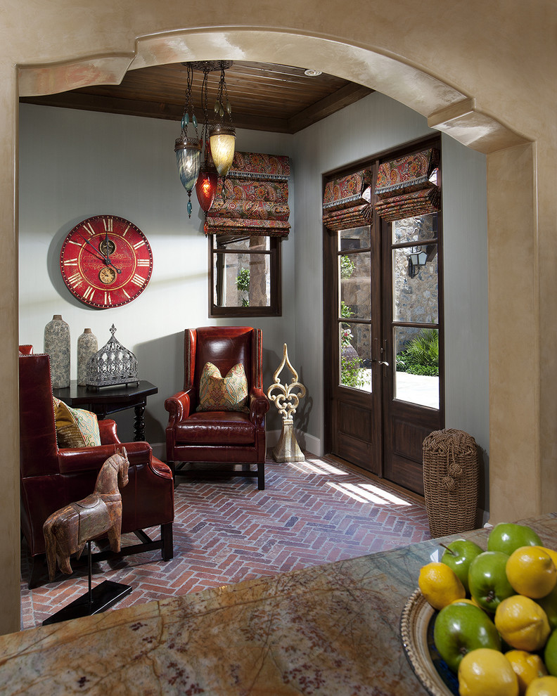 Example of a small tuscan brick floor and red floor living room design in Phoenix with gray walls