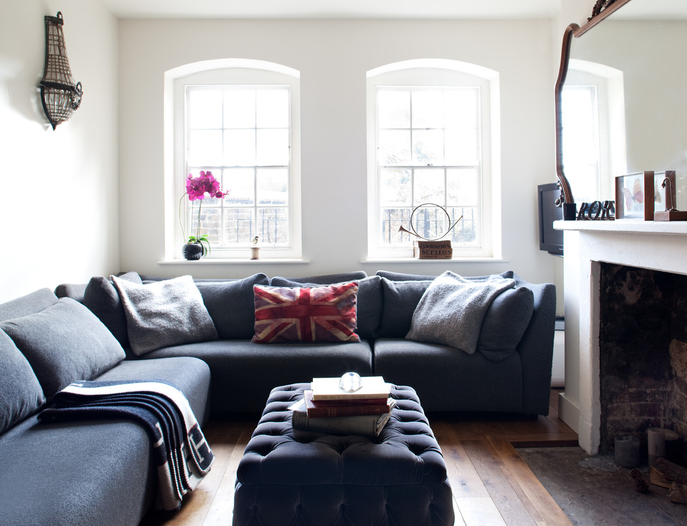 Living room - small eclectic enclosed medium tone wood floor living room idea in London with white walls and a standard fireplace