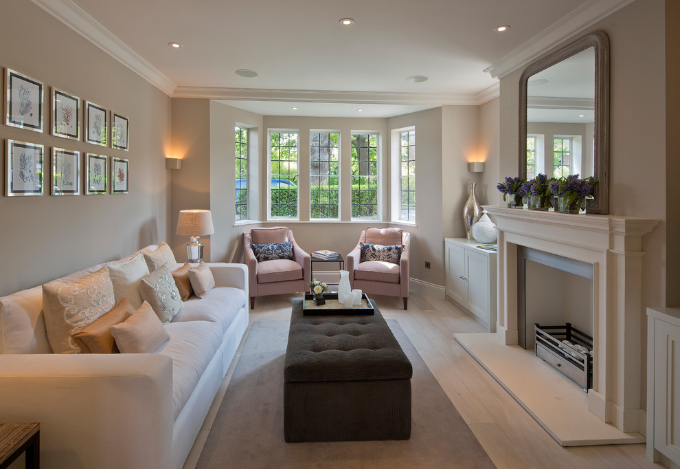 Living room - transitional enclosed living room idea in London with beige walls and a standard fireplace