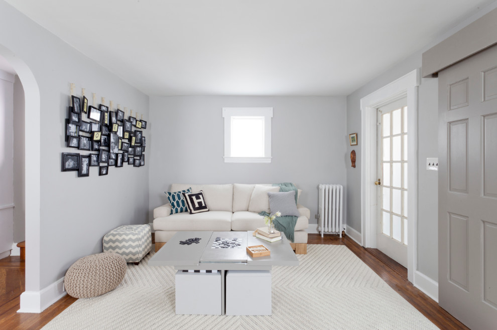 Example of a transitional living room design in New York with gray walls