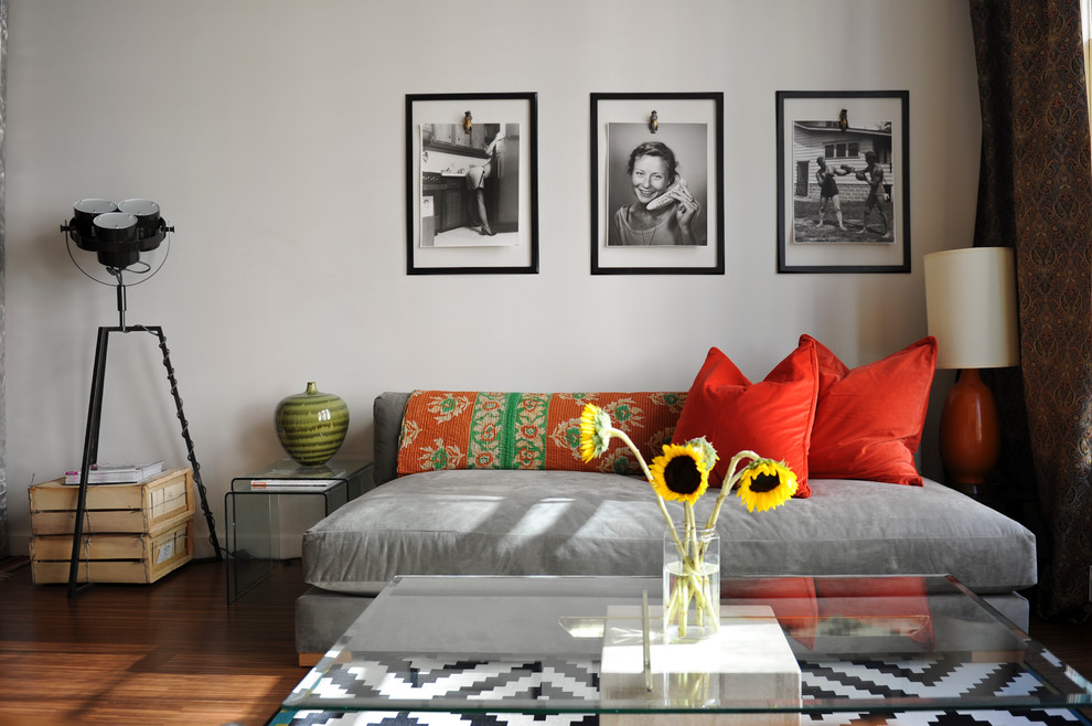 Eclectic medium tone wood floor living room photo in Vancouver with white walls