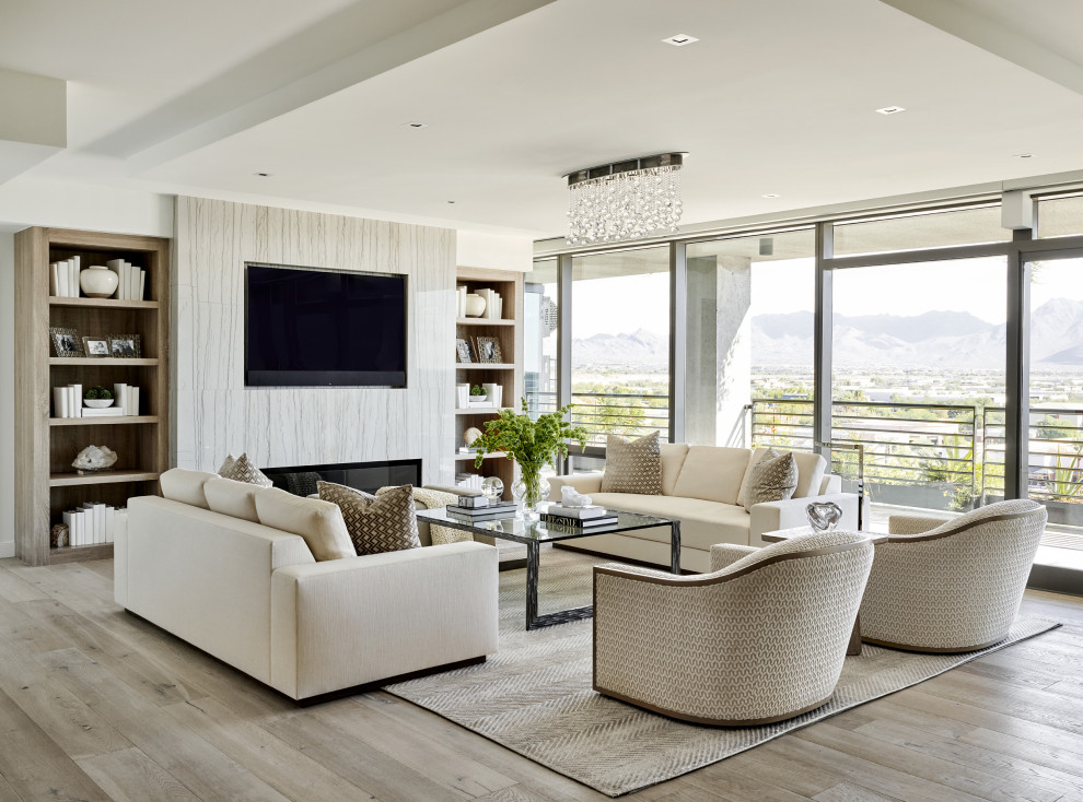 Large trendy open concept light wood floor and beige floor living room photo in Phoenix with white walls, a ribbon fireplace, a tile fireplace and a media wall