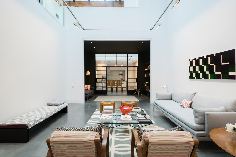 Inspiration for a large industrial concrete floor living room library remodel in London with white walls