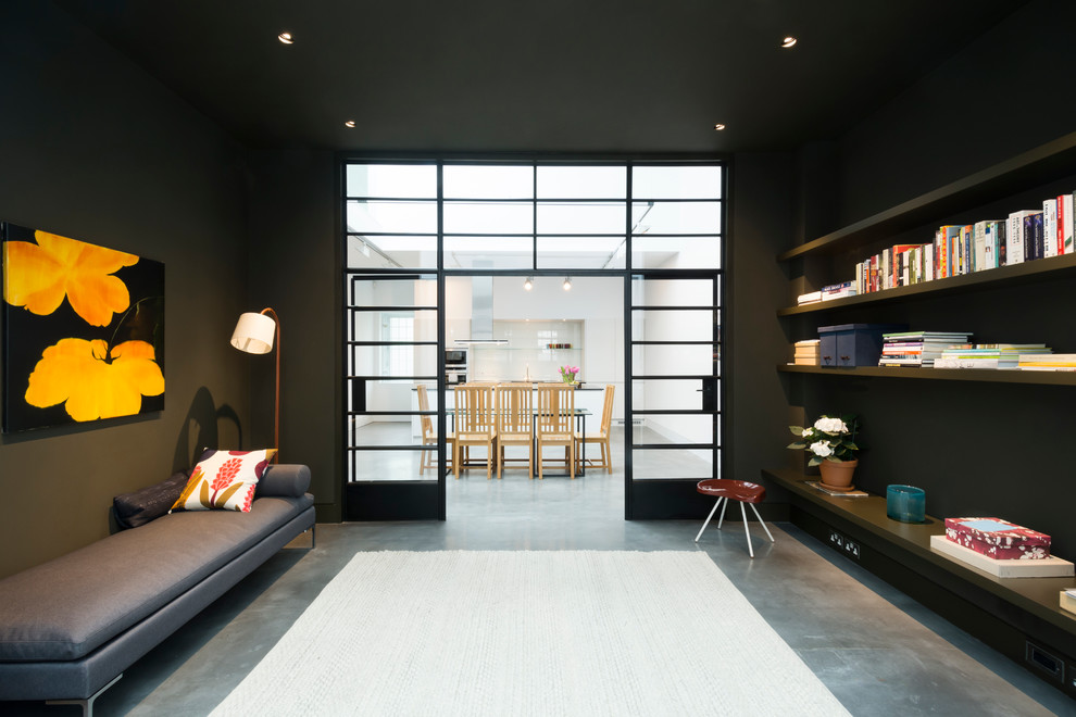 Living room library - huge industrial open concept concrete floor living room library idea in London with black walls