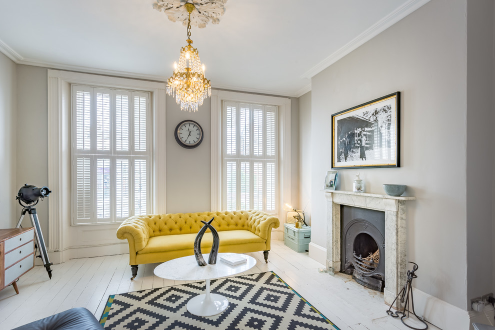 Mid-sized eclectic enclosed painted wood floor and white floor living room photo in London with gray walls, a standard fireplace and a stone fireplace