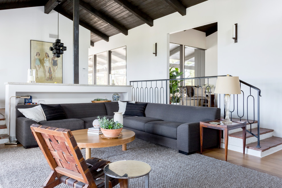 1950s open concept medium tone wood floor and brown floor living room photo in Los Angeles with white walls