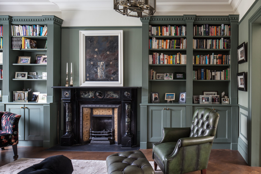 Living room - mid-sized traditional enclosed dark wood floor and brown floor living room idea in London with green walls, a standard fireplace and a metal fireplace