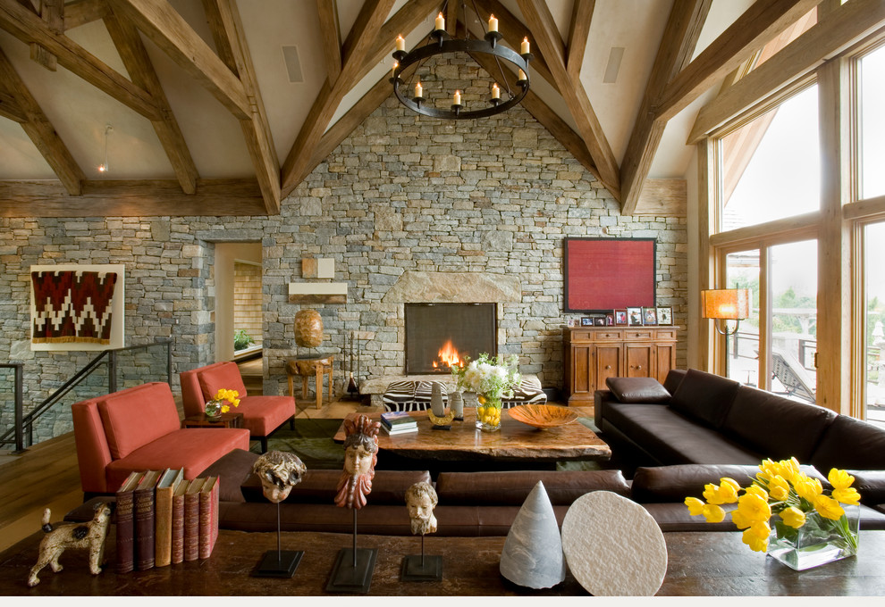Inspiration for a rustic formal and loft-style medium tone wood floor living room remodel in New York with a standard fireplace, a stone fireplace and no tv
