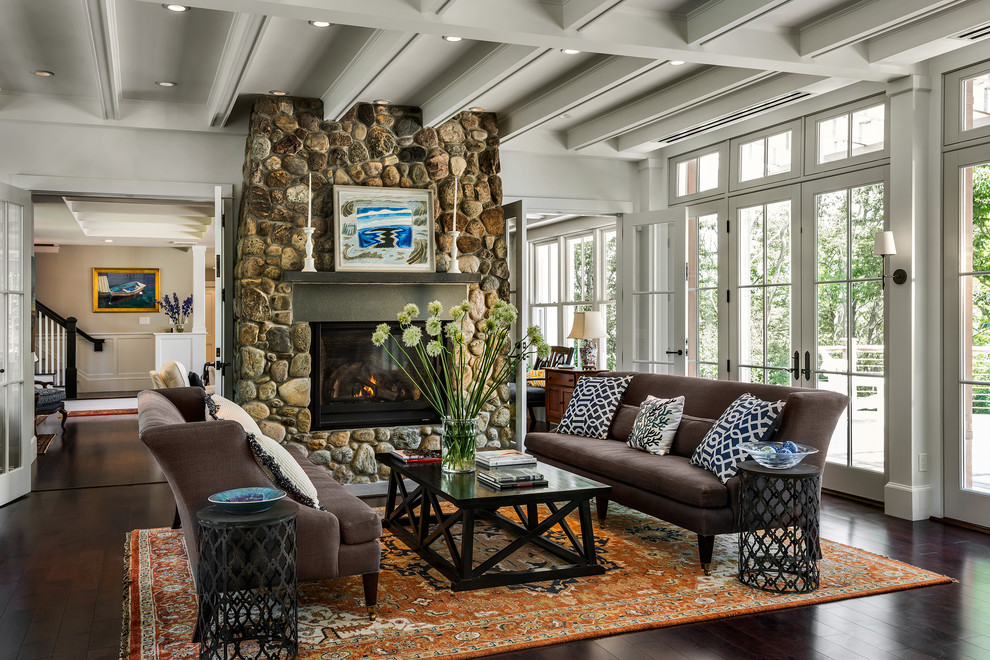 Example of a coastal dark wood floor living room design in Portland Maine with a standard fireplace and a stone fireplace