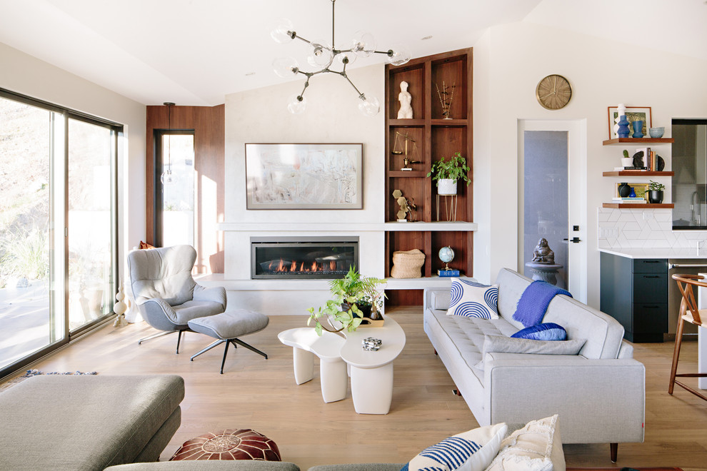 Example of a trendy formal and open concept medium tone wood floor and brown floor living room design in Vancouver with white walls, a ribbon fireplace and no tv