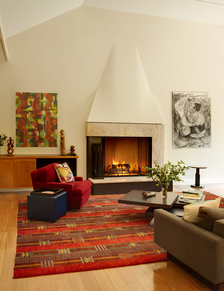Large trendy open concept medium tone wood floor and brown floor living room photo in New York with a stone fireplace, beige walls, a standard fireplace and a wall-mounted tv