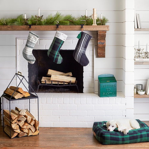 Holiday Decor Ideas for Dog Lovers -White brick firepalce with green plai stocking hanging from mantle.  White dog lying on green and navy plaid dog bed