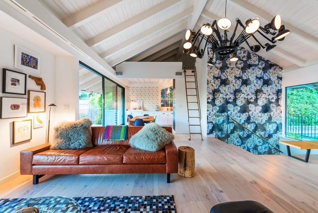 Idée de décoration pour un petit salon mansardé ou avec mezzanine bohème avec un mur multicolore, un sol en bois clair, une cheminée d'angle, un manteau de cheminée en plâtre, un téléviseur fixé au mur et un sol beige.