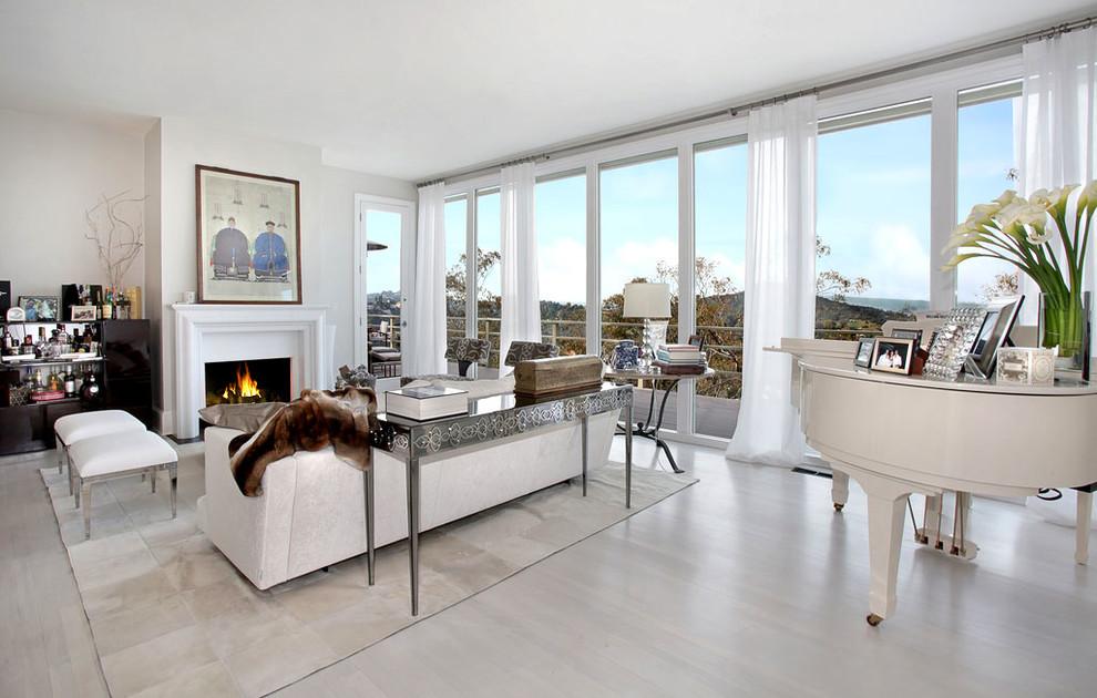 Foto di un grande soggiorno design aperto con angolo bar, parquet chiaro, camino classico e cornice del camino in intonaco