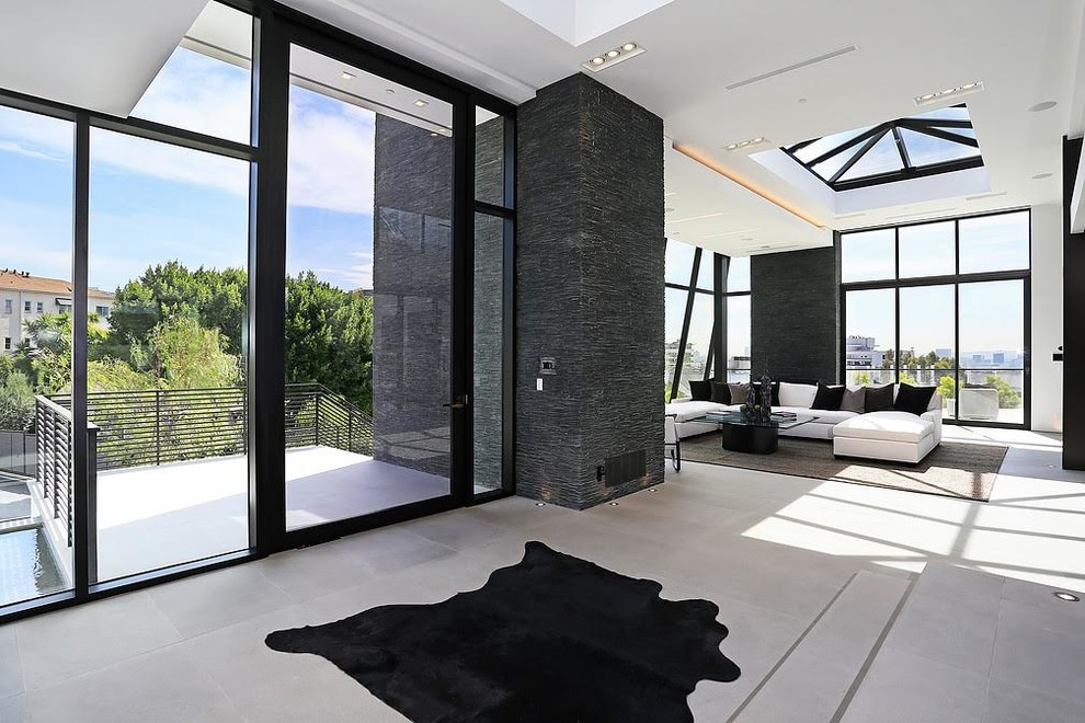 Inspiration for a huge contemporary formal and open concept concrete floor living room remodel in Los Angeles with white walls, a ribbon fireplace, a stone fireplace and a wall-mounted tv