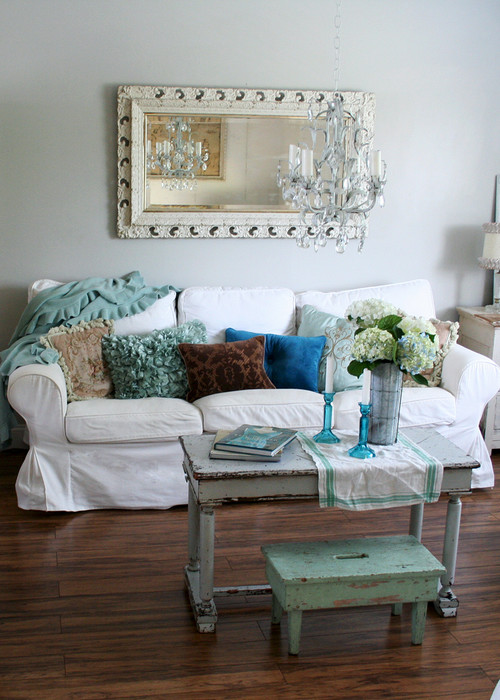 shabby chic living room with a slip covered sofa a worn table and
