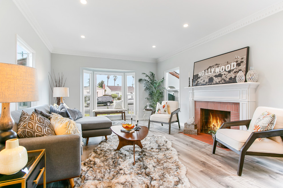 Living room - transitional light wood floor and beige floor living room idea in Los Angeles with gray walls, a standard fireplace and a brick fireplace