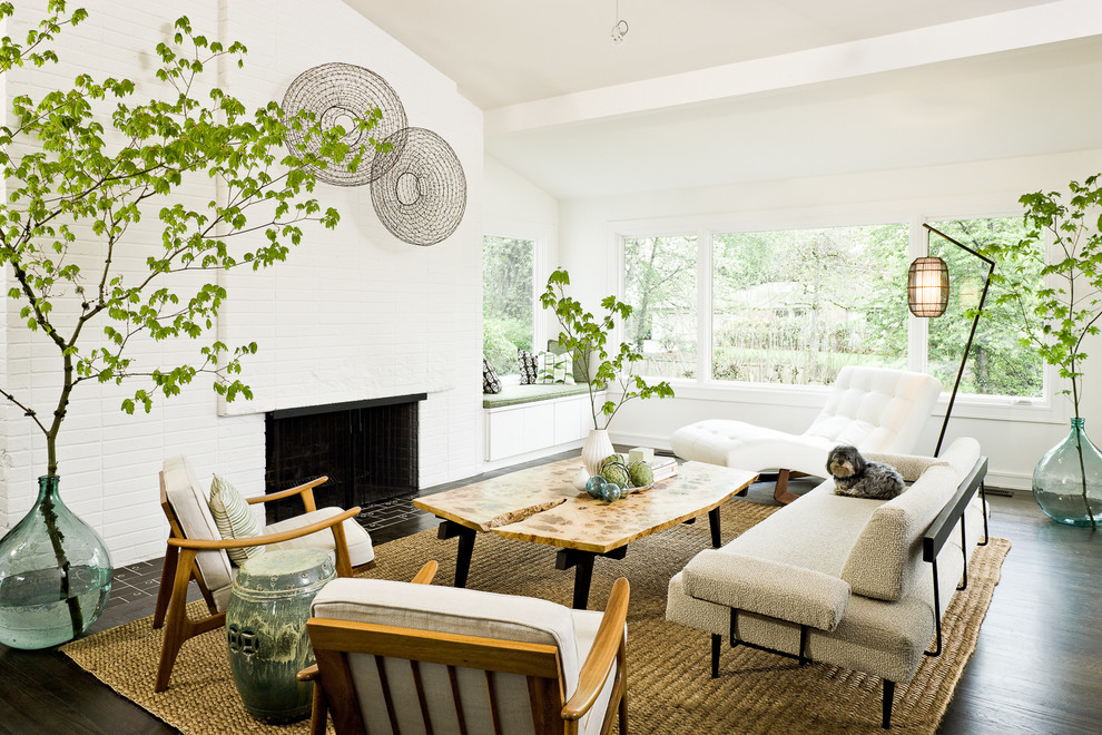 This is an example of a midcentury living room in Portland with white walls, a standard fireplace and a brick fireplace surround.