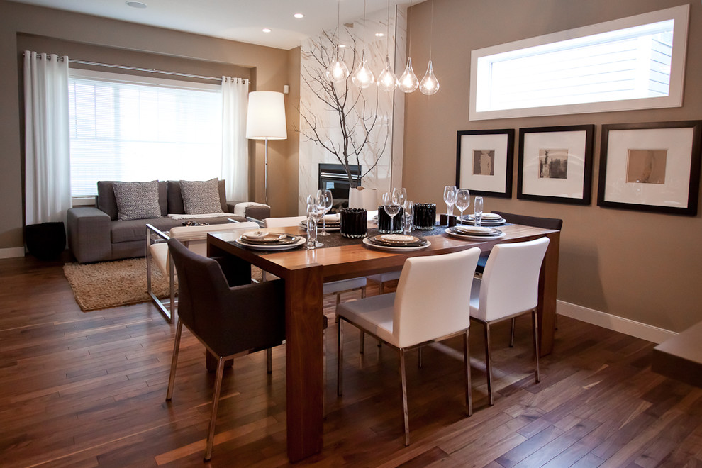 Inspiration for a small contemporary open concept medium tone wood floor living room remodel in Calgary with brown walls, a standard fireplace and a tile fireplace