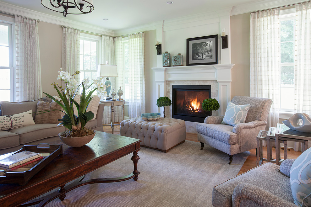 Inspiration for a large transitional formal medium tone wood floor and brown floor living room remodel in Boston with beige walls, a standard fireplace, a stone fireplace and no tv