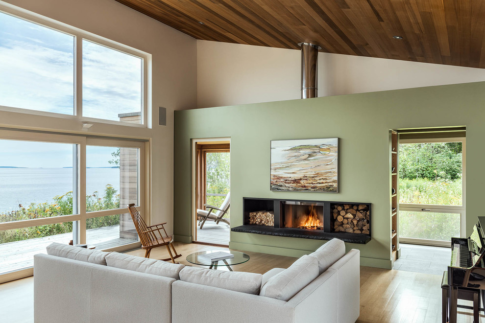 Example of a mountain style open concept light wood floor living room design in Other with green walls and a wood stove