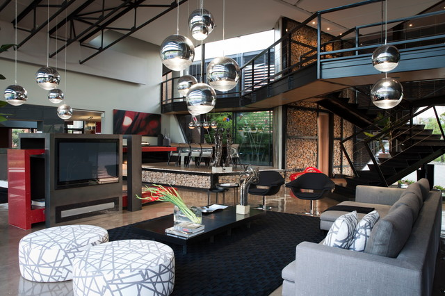 Trendy open concept concrete floor living room photo in Other with gray walls, no fireplace and a media wall
